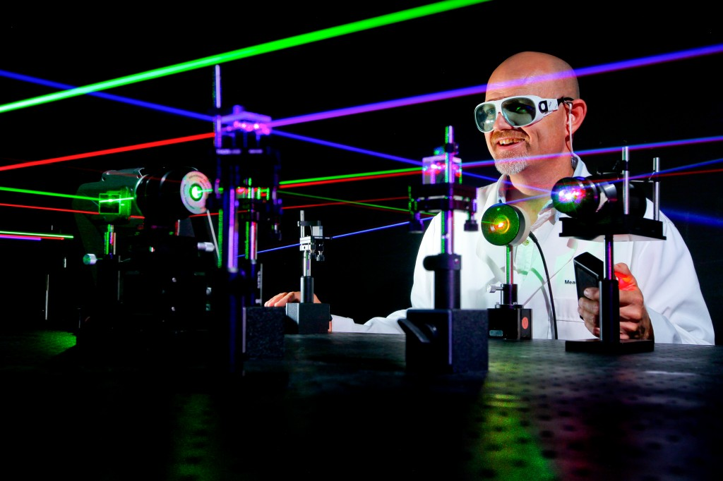 A labcoat wearing dude staring at coloured lazers through lazor safety glasses. YOLO, BOII